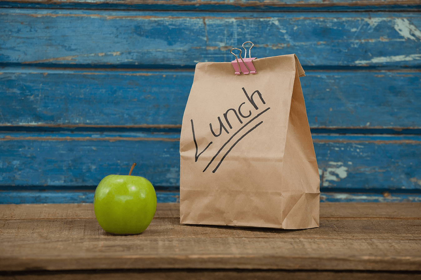 Green apple and brown paper bag with the word lunch on it.